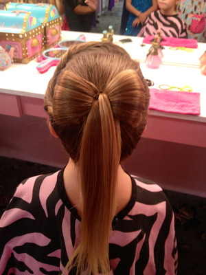 Hair bow with the rest of the ponytail hanging loose.