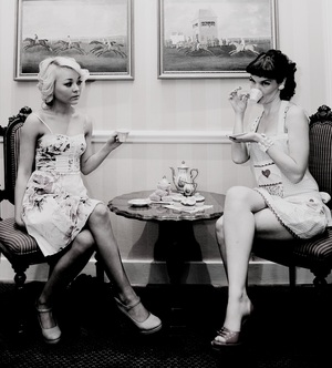 two friends having a discussion over tea and cupcakes