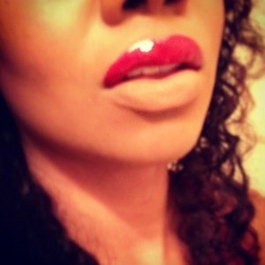 Red cream lipstick on upper lip topped with red shimmer gloss; lower lip blotted with foundation and powder.