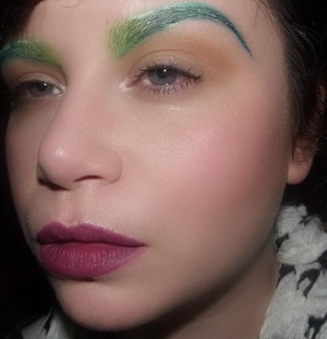 Bold green ombre eyebrows paired with a matte purple lip, cool pink complexion and neutral eyes.