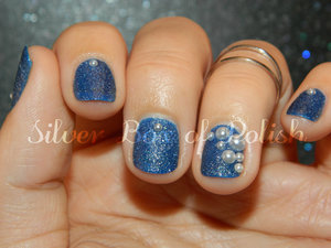 Blue textured nails with 3d pearl accents.