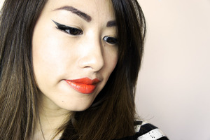Winged Eyeliner and Orange Lipstick.  Tutorial on how to do the Cateye look on my blog athttp://kakabeautyblog.com/2013/08/04/step-by-step-how-to-do-the-cateye-or-winged-eyeliner-look/