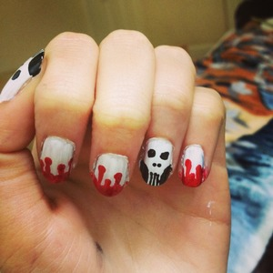 Very first attempt at any sort of nail art, skull faces on the thumb and ring finger, and dripping red blood on the other fingers, with white base coat.