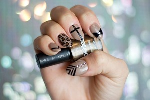 a classy almond shape acrylic tip overlay featuring some fun, edgy nail art on top of a chic khaki polish