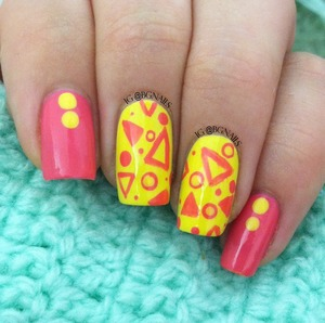 A very cute manicure using pink and yellow polish with triangles and circles as the main designs.