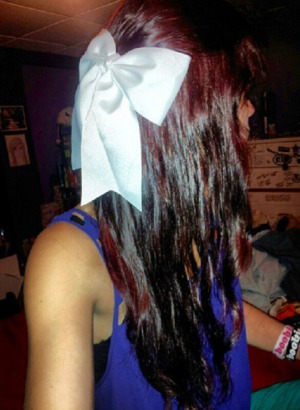 red hair, curled, top pulled back with bow