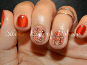 A manicure in orange and nude with glitter and studs.