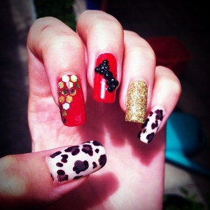 Gold glitter, leopard print and red nails decorated with black rhinestones and gold holograms
