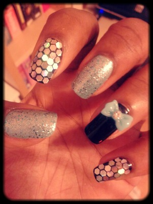 Black and mint blue nails with glitter over it and also hex glitter and a bow design