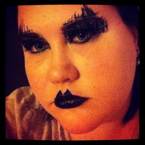 Black eyeshadow, black liquid eyeliner, false lashes, black lipstick