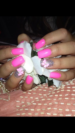 Sparkly and neon pink nails with a cute bow added to the ring finger