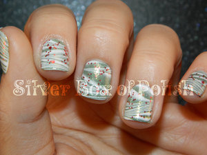 Green and white marbled nails topped with a festive glitter.
