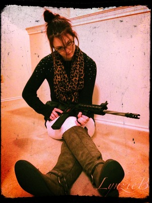 White skinny jeans, wanted boots, black studded sweater, leopard print scarf, and my lovely Miss Bomber AR 15.