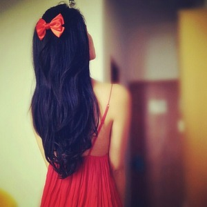 Red bow in a black wavy hair.