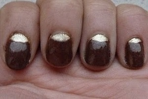 A dark brown manicure with a golden moonmani.