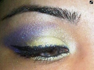 Darker purples in the crease and corner of lower lid..white to highlight brow bone...yellow on top and bottom lid...blend well..line top bottom and waterline with black liner and use a black glitter liner on top of black liner on top lid and mascara to finish and walla!!! Your done! :)