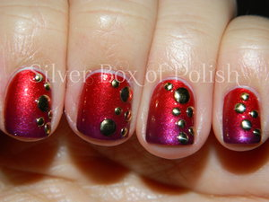 Gradient nails decorated with round metal studs in varying sizes.