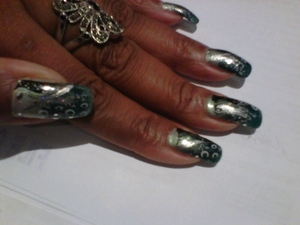 I applied 3 shades of blue and created a gradient from light to dark.  I used a stamp to create the black wave and the white half circles and completed my design with a silver nail paint and glitter.