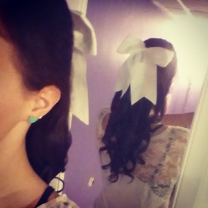 curled and half pulled back with a big white bow