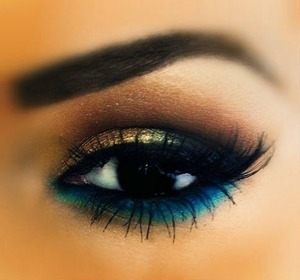 Golden shadow with a delicate black eye liner on top lid with a dark blue liner on bottom lid with turquoise liner underneath dark blue