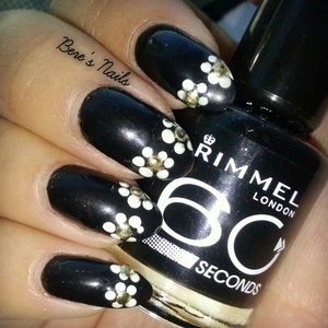 A black base with simple daisy accents and round gold studs in the middle.