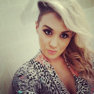 Vintage Leopard print shirt,Side of head Shaved , Blonde hair with a loose curl, smokey eye, eyebrows shaped, fake lashes