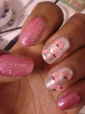 Pink nail polish with pink glitter over it and a sparkly white polish with butterfly fimos