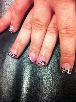 Acrylic nails with tips, with leopard print design, with one nail split in half with glitter and leopard print.