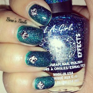 A swatch of this dark green holographic! accented all the nails with a square black and white splattered stud.