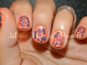 Orange and purple manicure created by dripping wet polish into wet polish.