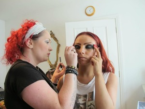 This is while working on a music video. The girls all wore gems on their faces.