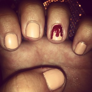 "Spice up your Halloween with these gory and stylish nails! I used a nude color (you can also use white!) for my base (Pure Ice in ""Nude Beach"") and then a berry red color (LA Colors in ""Berry Red""). I used a small nail dotting tool and basically dragged the red down my nail to make it look like it's dripping down my nail! You can do this on all of your nails but I just did it on my accent nail for a subtle (and cheap!) Halloween mani. (:"