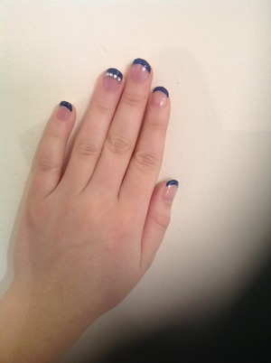 Navy French manicure with rhinestone detail on ring finger