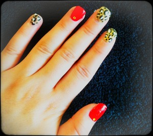 Gold leopard print nails with red ring and thumb. Yellow rhinestones placed on red nails.