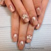 Nude nails with silver bow charm