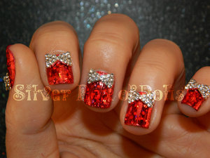 A holiday nail look featuring nail foils and rhinestone bows.