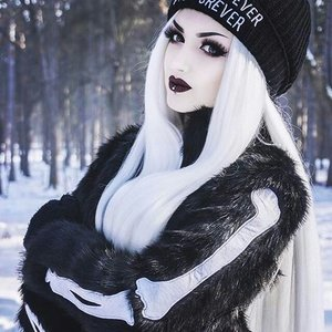 Goth-like makeup of contrasting lights and darks creating an intense and sharp look that's not too harsh or overwhelming.