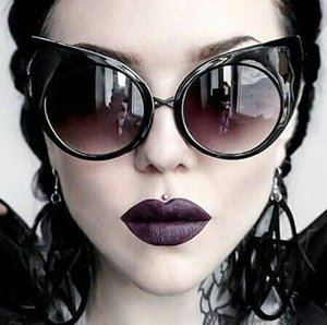 Intensely dark, blackish-purple lips with matte finish looks awesome. Add the extremely sharp edges circumscribing the lips and you have an absolutely stunning look. Not to mention the funky sunglasses.