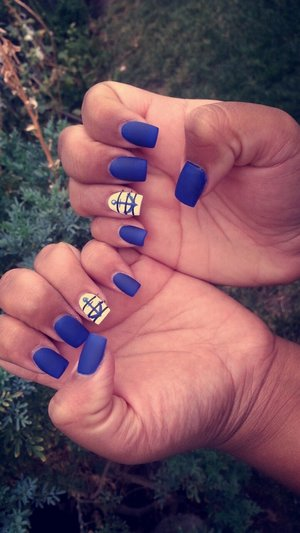 Matte royal blue nails with the ring finger being white with black stripes and a blue anchor
