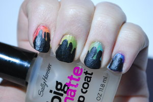 I sponged red, orange, yellow, green, blue and purple polishes onto my nails to get the gradient, then I used black acrylic paint and a small detail brush that I purchased at Hobby Lobby to draw the drips, then filled it in and topped everything off with a matte top coat