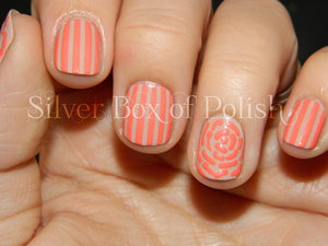 Nail art with clean stripes and a simple floral accent.