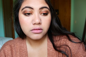 Simple burnt orange eyeshadow, brown in the crease, and golden glitter on the lid, rosy cheeks and pale pink lips.