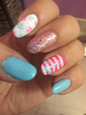 Light blue and hot pink nautical nails with glitter.