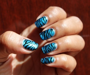 A simple nail design using a blue base colour with black acrylic paints for the stripes!