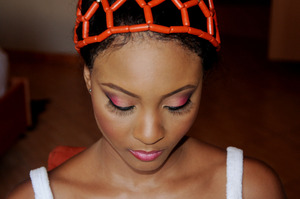 Traditional Benin bridal Makeup look, Bold eyeshadow colors, with golds, reds, and purples. winged eyeliner and false lashes.