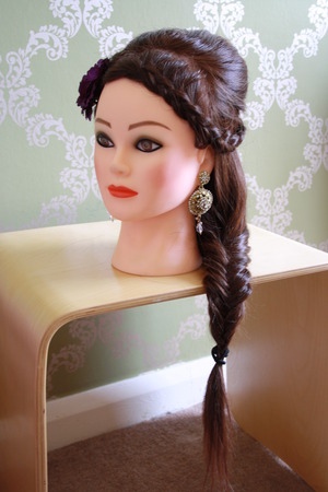 Reverse french braid on the front section of hair with a section of back combing, finished of with a fish plait and floral decoration.