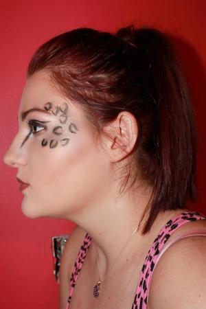 Leopard-inspired makeup with liquid eyeliner, cheek contour, and burnt orange lips