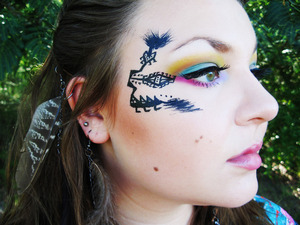 For this look, I used a variety of eyeshadows from multiple palettes and individual shadows from quite a few different companies, some high end, some low end. My foundation is Make Up For Ever's Mat Velvet in Natural Beige (40) and I made the tribal designs using Urban Decay's 24/7 Liner, the black one. My lashes are just some cheap Halloween lashes I've had for the longest time but never used. Silly me. :)