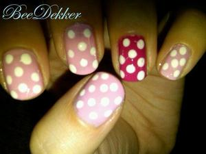 Using a light and a dark pink polish paint 4 nails the light shade and 1 the dark shade. Using a dotting tool apply medium white dots to your nails.