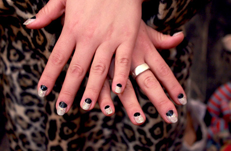 Tate is sporting holiday half moons created with Essie black polish, and a mix of Cynthia Rowley and Japanese glitter polishes.